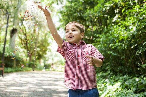 Happy boy playing with confetti - VABF000555