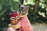 Mother and little son with animal masks playing in the park - VABF000564