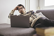 Man lying on a couch looking at laptop - LCUF000018