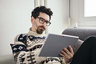 Portrait of pensive man using digital tablet - LCUF000024