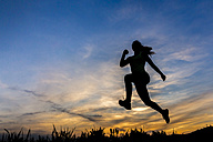 Silhouette of female jogger at sunset - STSF001017