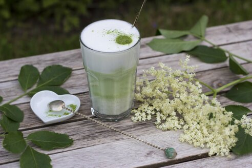 Matcha tea with milk in glass on wood, elder flowers and heart shaped porcellain bowl with spoon - YFF000547