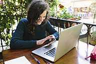 Young woman sitting on balcony using laptop - BOYF000373