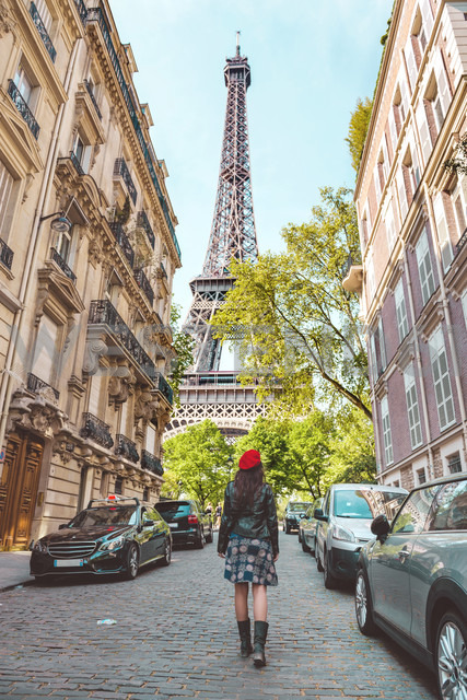 France, Paris, Eiffel Tower among the buildings, nearby street and woman wearing a red beret walking on the street - GEMF000914 - Gemma Ferrando/Westend61