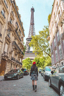 France, Paris, Eiffel Tower among the buildings, nearby street and woman wearing a red beret walking on the street - GEMF000914