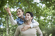 Young man carrying his girfriend piggyback in the nature - ZEF008672