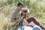 Young man playing guitar for his girlfriend in field - ZEF008675