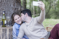 Happy young couple having a picnic with white wine taking a selfie - ZEF008678