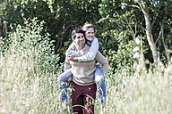 Young man carrying his girfriend piggyback in the nature - ZEF008681