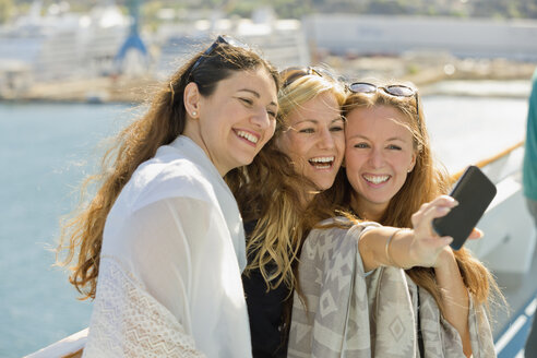 Three happy women taking a selfie on a cruise ship - ONBF000067