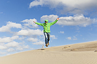 Enthusiastic mature man jumping over sand dune - GWF004734