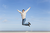 Enthusiastic mature woman jumping on beach - GWF004737