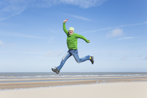 Enthusiastic mature man jumping on beach - GWF004740