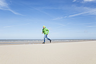 Mature man running on beach - GWF004743