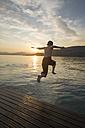 Italy, Veneto, Bardolino, Lake Garda, boy jumping into the water at sunset - SARF002735