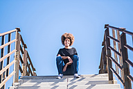 Portrait of smiling woman sitting on stairs - SIPF000526