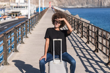 Portrait of smiling woman sitting on her rolling suitcase on a jetty - SIPF000529