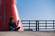 Young woman sitting on deck reading a book - SIPF000532