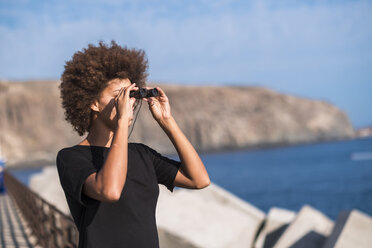 Spain, Tenerife, young woman on a jetty looking at distance with binocular - SIPF000535
