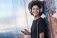 Portrait of happy young woman with headphones and smartphone leaning against wall - SIPF000538