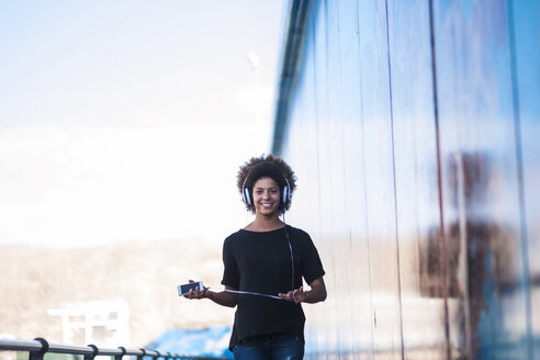 Portrait of smiling young woman with headphones and smartphone - SIPF000541