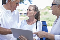 Elderly couple with fitness instructor on digital tablet - ZEF008686