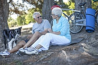 Elderly couple sitting outdoors with dog and bicycles - ZEF008704