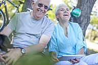 Happy elderly couple sitting outdoors with digital tablet - ZEF008707
