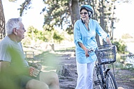 Elderly woman with bicycle and senior man having a break in forest - ZEF008710