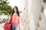 Young woman with shopping bags holding smart phone - JASF000793