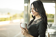 Young woman standing at the window drinking coffee - JASF000808