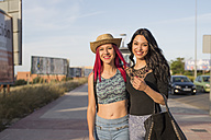 Two pretty girls walking in street with arms around - JASF000814