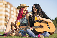 Friends sitting on grass playing guitar - JASF000817