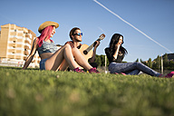 Friends sitting on grass playing guitar - JASF000820