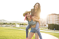 Two girl friends playing piggy back in park - JASF000832
