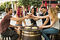 Friends in a bar toasting with beer glasses - JASF000844