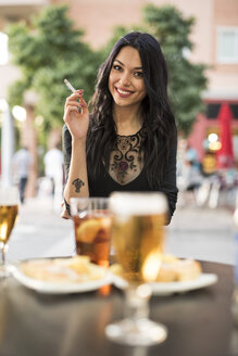 Young woman smoking cigarette in bar - JASF000847