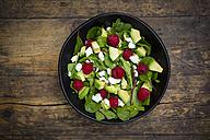 Bowl of avocado raspberry salad with feta on dark wood - LVF004944