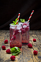Raspberry champagne in glasses, drinking straw, mint and raspberries - LVF004947