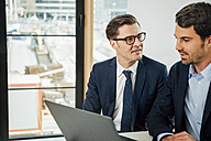 Two businessmen with laptop talking in office - CHAF001766