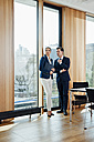 Businessman and businesswoman in office talking at the window - CHAF001769