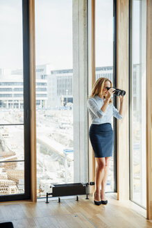 Businesswoman with binoculars looking out of window - CHAF001778