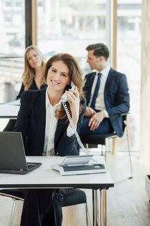Smiling businesswoman at office desk on the phone - CHAF001787