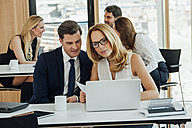 Businessman and businesswoman working together at office desk - CHAF001793