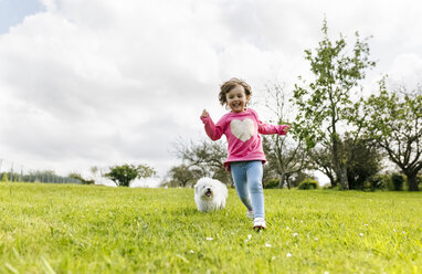 Smiling little girl running on a meadow with her dog - MGOF001923