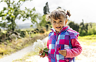 Portrait of smiling little girl with flower in her hand - MGOF001929