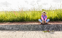 Laughing little girl sitting on pavement in front of a meadow - MGOF001944