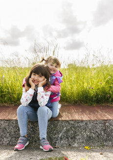 Portrait of two little sisters sitting on pavement in front of a meadow - MGOF001947
