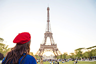France, Paris, Champ de Mars, back view of woman wearing red beret looking at Eiffel Tower - GEMF000918