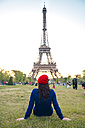 France, Paris, Champ de Mars, back view of woman sitting on meadow  looking at Eiffel Tower - GEMF000921